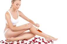 depilation of female legs with waxing on white background. profile of woman getting legs waxed for hair removal near scattered petals