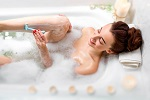 Young and positive woman shaving her legs in the bath with foam and candles.