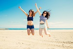 Happy and funny girl friends jumping on the beach, Some blur on legs beacuse of movement
